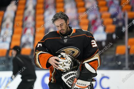 Anaheim Ducks goaltender Ryan Miller takes off his mask during the first period of an NHL hockey game against the Arizona Coyotes, in Anaheim, Calif