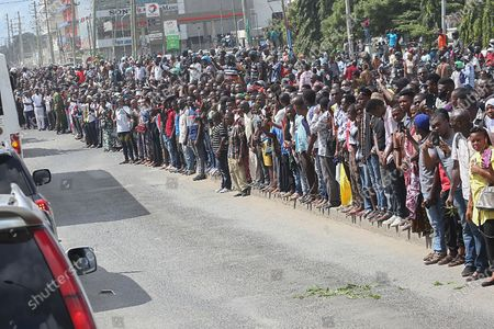 Tanzanians line a street to get a glimpse of the body of president John Magufuli passing in a convoy in Dar es Salaam, Tanzania 20 March 2021 (issued 22 March 2021). According to Tanzania police at least 4 have died including children during a stampede by mourners trying to view the body of President John Magufuli on 21 March 2021. President John Magufuli  died on 17 March 2021 at the age of 61.