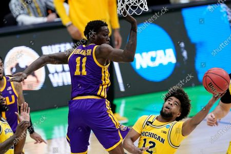 Michigan guard Mike Smith (12) drives to the basket around LSU forward Josh LeBlanc Sr. (11) during the second half of a second-round game in the NCAA men's college basketball tournament at Lucas Oil Stadium, in Indianapolis