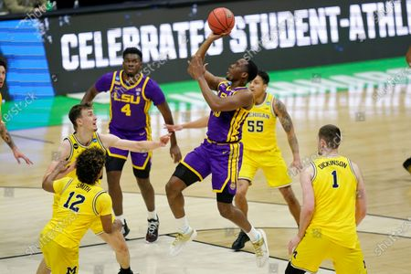 Guard Aundre Hyatt, center, drives to the basket over Michigan defenders Franz Wagner, left, Mike Smith (12) and Hunter Dickinson (1) during the first half of a second-round game in the NCAA men's college basketball tournament at Lucas Oil Stadium, in Indianapolis