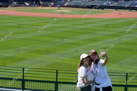 Stock Photo of Amber Herrin, right, of San Diego, takes a selfie with her daughter, Eva Lopez, as they wait for a spring training baseball game between the Kansas City Royals and the San Diego Padres, in Surprise, Ariz