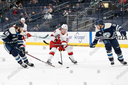 Carolina Hurricanes' Brock McGinn, center, carries the puck across the blue line between Columbus Blue Jackets' Ryan MacInnis, left, and Michael Del Zotto during the first period of an NHL hockey game, in Columbus, Ohio
