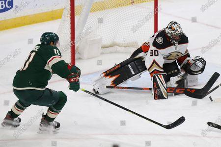 Anaheim Ducks' goalie Ryan Miller (30) stops the puck shot by Minnesota Wild's Zach Parise (11) during the third period of an NHL hockey game, in St. Paul, Minn. Minnesota won 2-1