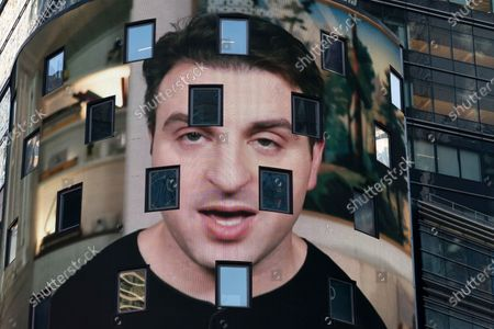 Brian Chesky, CEO of Airbnb, is shown on an electronic screen at the Nasdaq MarketSite in New York. Airbnb Inc. is being asked to drop its sponsorship connections to 2022 Beijing Winter Olympics by a coalition of 150 human-rights campaigners. The coalition is headed by groups that oppose rights violations in China including widely reported genocide against Muslim Uyghurs in the Xinjiang region. An open letter sent on to Chesky argues that Airbnb is trying to drive tourism in China at the expense of Uyghurs and Tibetans who cannot travel freely in the country