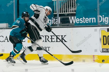 Los Angeles Kings center Anze Kopitar, right, skates for the puck against San Jose Sharks defenseman Mario Ferraro (38) during the second period of an NHL hockey game in San Jose, Calif