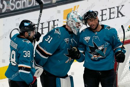San Jose Sharks defenseman Mario Ferraro, from left, celebrates with goaltender Martin Jones and left wing Evander Kane after the Sharks defeated the Los Angeles Kings in an NHL hockey game in San Jose, Calif