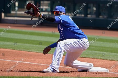 Kansas City Royals first baseman Carlos Santana takes a throw during a spring training baseball game against the San Diego Padres, in Surprise, Ariz