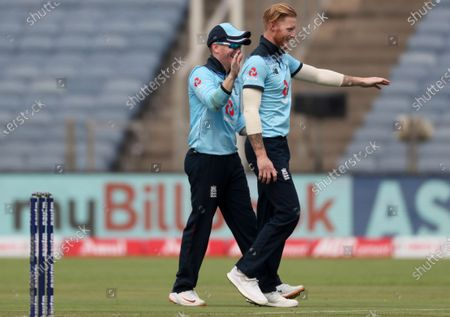 England's captain Eoin Morgan, left, congratulates teammate Ben Stokes on dismissing India's Rohit Sharma during the first One Day International cricket match between India and England at Maharashtra Cricket Association Stadium in Pune, India