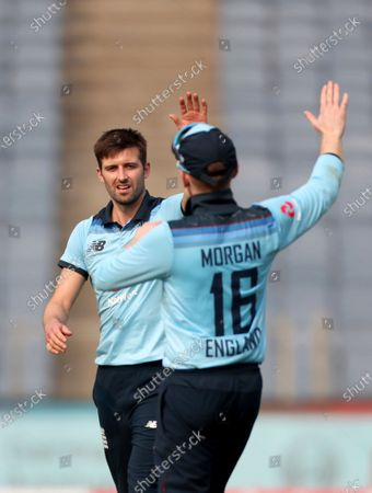 England's Mark Wood, left, celebrates with captain Eoin Morgan after the dismissal of India's Shreyas Iyer during the first One Day International cricket match between India and England at Maharashtra Cricket Association Stadium in Pune, India