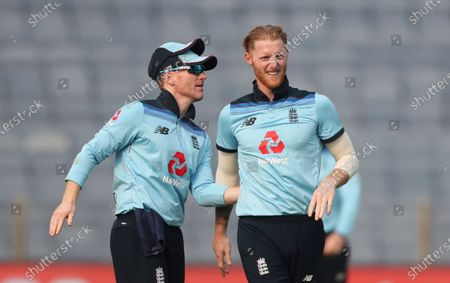 England's Ben Stokes, right, celebrates with captain Eoin Morgan after dismissing India's Shikhar Dhawan during the first One Day International cricket match between India and England at Maharashtra Cricket Association Stadium in Pune, India