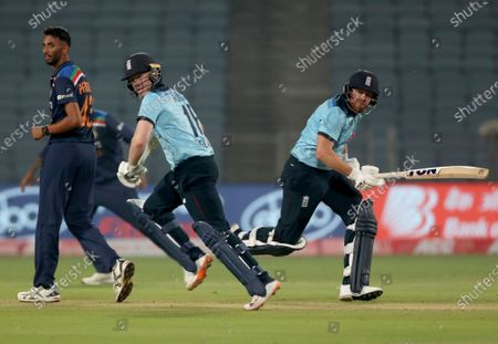 India's Prasidh Krishna, left, watches as England's Jonny Bairstow, right, and captain Eoin Morgan run between the wickets to score during the first One Day International cricket match between India and England at Maharashtra Cricket Association Stadium in Pune, India