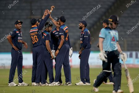 India's Shardul Thakur, third left without cap, celebrates with teammates the dismissal of England's captain Eoin Morgan, right, during the first One Day International cricket match between India and England at Maharashtra Cricket Association Stadium in Pune, India