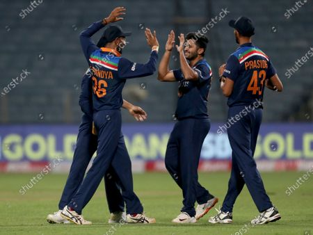 India's Shardul Thakur, second right, celebrates with teammates the dismissal of England's captain Eoin Morgan during the first One Day International cricket match between India and England at Maharashtra Cricket Association Stadium in Pune, India