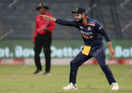 India's captain Virat Kohli celebrates the dismissal of England's captain Eoin Morgan during the first One Day International cricket match between India and England at Maharashtra Cricket Association Stadium in Pune, India