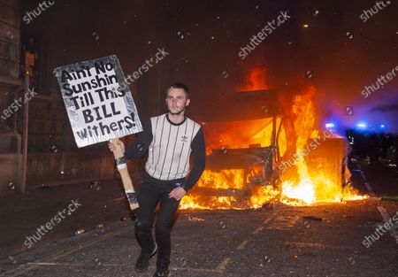 "; Bristol, UK. Protestors watch and pose with a sign which is a pun on both the Police, Crime, Sentencing and Courts Bill and a song by Bill Withers, in front of a police van which has been set on fire as police clash with protesters outside New Bridewell Police Station on Sunday evening during a ""Kill the Bill"" protest against Police, Crime, Sentencing and Courts Bill takes place through the centre of Bristol during the Covid-19 coronavirus pandemic in England. The Bill proposes new restrictions on protests. Lockdown restrictions have been partly lifted to allow people to gather outdoors socially in households, bubbles, or to meet one person from another household, but the police say protests are not allowed under the current Covid regulations."