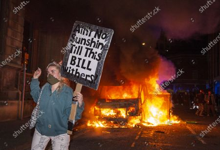 "Stock Picture of ; Bristol, UK. Protestors watch and pose with a sign which is a pun on both the Police, Crime, Sentencing and Courts Bill and a song by Bill Withers, in front of a police van which has been set on fire as police clash with protesters outside New Bridewell Police Station on Sunday evening during a ""Kill the Bill"" protest against Police, Crime, Sentencing and Courts Bill takes place through the centre of Bristol during the Covid-19 coronavirus pandemic in England. The Bill proposes new restrictions on protests. Lockdown restrictions have been partly lifted to allow people to gather outdoors socially in households, bubbles, or to meet one person from another household, but the police say protests are not allowed under the current Covid regulations."
