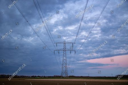 High voltage electricity poles during magic hour. The metal towers as seen in the sunset in the Dutch countryside distribute electric energy from the power station, Belgium and Germany across the country. The electric wires, the grid and pillars or power pylons are seen as silhouettes in the colorful cloudy dusk sky. Stevensweert, the Netherlands on March 19, 2021