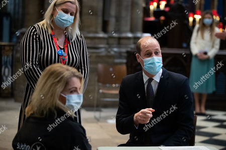 Prince William speaks to a member of staff with Pippa Nightingale (back left), chief nurse at Chelsea and Westminster Hospital NHS Foundation Trust, during a visit to the vaccination centre at Westminster Abbey, London, to pay tribute to the efforts of those involved in the Covid-19 vaccine rollout.