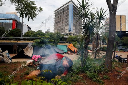 Carolina Baez, a farmer from Caaguazu, blows on a fire where protesters are camped in a downtown square calling for the resignation of President Mario Abdo Benitez over his handling of the new coronavirus pandemic and the state of the public health system, in Asuncion, Paraguay