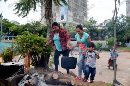 Farmers from Caaguazu carry a pot to a campfire in a downtown square where protesters have set up an encampment calling for the resignation of President Mario Abdo Benitez over his handling of the new coronavirus pandemic and the state of the public health system, in Asuncion, Paraguay