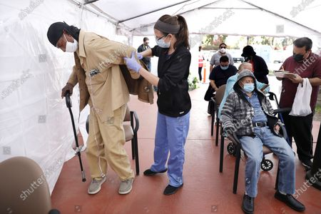 Stock Image of James Smith, 64, of Los Angeles, left, gets help with his jacket after receiving his vaccination by nurse practitioner Laura Fisher, center, at Kedren Community Health Center in South Los Angeles on Monday, March 22, 2021. (Christina House / Los Angeles Times)