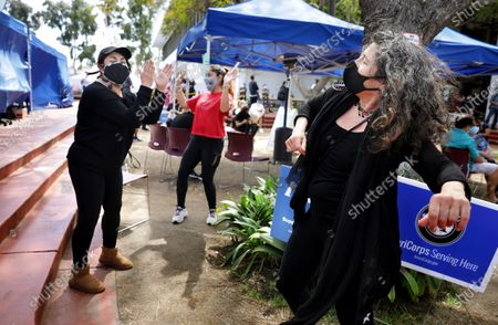 Laurie Ginsburg, 58, of Santa Monica, right, dances with Alma De La Rosa, 53, of South Gate, left, and De La Rosa's daughter Andrea, 27, center, after receiving the Covid-19 vaccine at Kedren Community Health Center in South Los Angeles on Monday, March 22, 2021. (Christina House / Los Angeles Times)