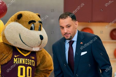 New University of Minnesota mens' head basketball coach Ben Johnson walks past university mascot Goldy Gopher after he met the media, in Minneapolis. Johnson replaces Richard Pitino, who was fired after eight seasons and took the job at New Mexico