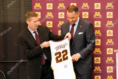 New University of Minnesota mens' head basketball coach Ben Johnson, right, receives his own number from athletic director Mark Coyle following a press conference to introduce Johnson, in Minneapolis. Johnson replaces Richard Pitino, who was fired after eight seasons and took the job at New Mexico