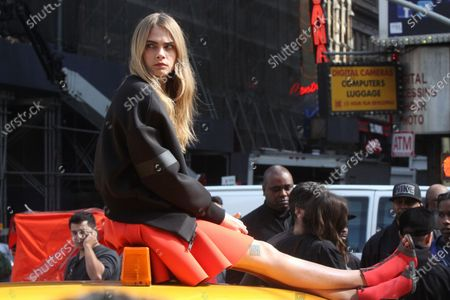 British fashion model Cara Delevingne shooting the new DKNY campaign in Times Square in New York City on October 14, 2013.  Photo Credit: Henry McGee/MediaPunch