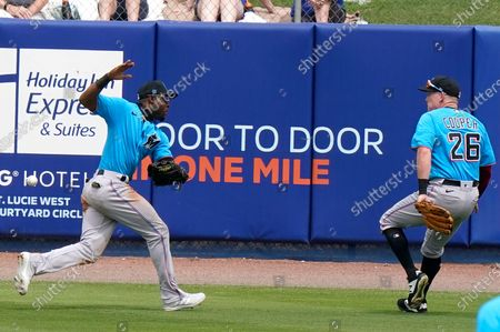 Miami Marlins center fielder Starling Marte, left, can't get to a ball hit by New York Mets' Brandon Nimmo for a triple during the third inning of a spring training baseball game, in Port St. Lucie, Fla. At right is Miami Marlins right fielder Garrett Cooper (26