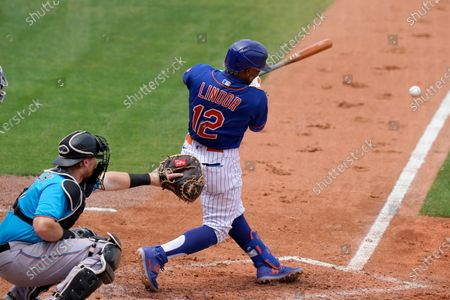 New York Mets' Francisco Lindor (12) hits an RBI double to score Brandon Nimmo during the third inning of a spring training baseball game against the Miami Marlins, in Port St. Lucie, Fla