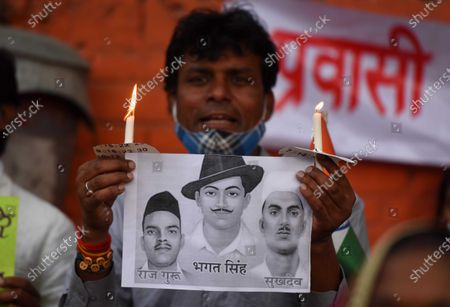 A migrant worker hold playcard of Bhagat Singh, Raj Guru and Sukhdev during candle protest  on anniversary of lockdown  under Working people's Charter and other workers organizations at Jantar Mantar on March 23, 2021 in New Delhi, India. They demanded compulsory registration of all migrant and informal workers in appropriate labour laws.