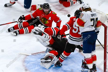 Chicago Blackhawks goaltender Kevin Lankinen, center, is knocked over as defensemen Duncan Keith (2) and Ian Mitchell, second from right, defend against Florida Panthers right wing Owen Tippett (74) during the third period of an NHL hockey game, in Chicago