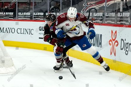 Arizona Coyotes center Christian Dvorak (18) steals the puck from Colorado Avalanche defenseman Jacob MacDonald (34) in the second period during an NHL hockey game, in Glendale, Ariz