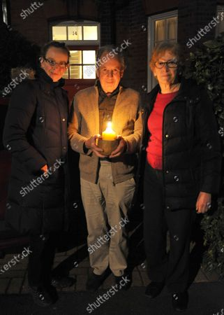 Stock Image of Rosalind Hardy,Tony Hardy and Gill Hardy,residents of Surbiton holding a candle as a beacon of remembrance for Covid victims tonight.