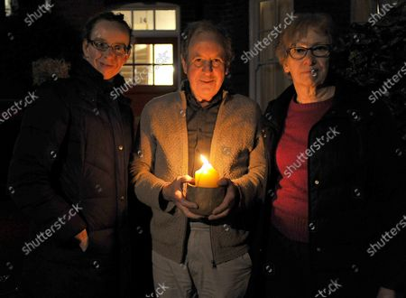 Rosalind Hardy,Tony Hardy and Gill Hardy,residents of Surbiton holding a candle as a beacon of remembrance for Covid victims tonight.