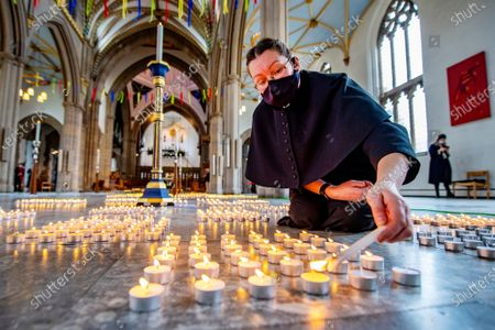 Stock Photo of 1st Anniversary of the National Lockdown in a Day of national reflection at Blackburn Cathedral, Lancs. Verger Rachel Fielding (pictured) . - More than 4000 candles are lit ,one for every Lancs life lost