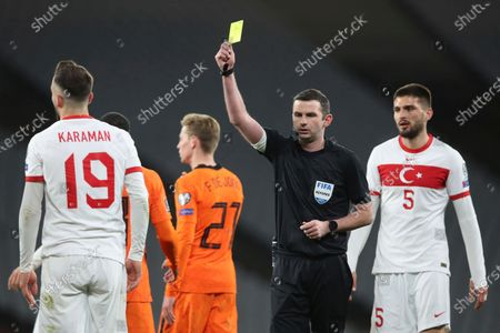 Referee Michael Oliver shows a yellow card to Turkey's Kenan Karaman, left, during the World Cup 2022 group G qualifying soccer match between Turkey and Netherlands at the Ataturk Olimpiyat Stadium in Istanbul, Turkey