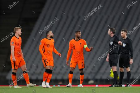 Netherlands' Georginio Wijnaldum, center, Netherlands' Memphis Depay, second left, and Netherlands' Matthijs De Ligt argue with referee Michael Oliver during the World Cup 2022 group G qualifying soccer match between Turkey and Netherlands at the Ataturk Olimpiyat Stadium in Istanbul, Turkey