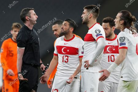 Turkey's cengiz Umut Meras, second left, argues with referee Michael Oliver during the World Cup 2022 group G qualifying soccer match between Turkey and Netherlands at the Ataturk Olimpiyat Stadium in Istanbul, Turkey