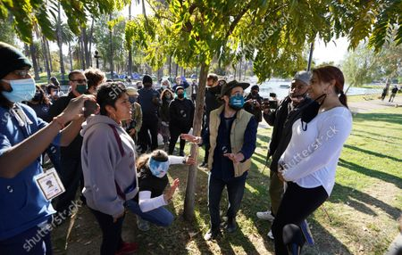 """An Echo Park resident, right, holding a baseball bat, expresses she carries it for her safety during her walk around the park, is surrounded by activists, as she argues with some of remaining residents of the Echo Park homeless encampment at Echo Park Lake in Los Angeles . Los Angels Council member Mitch O'Farrell, 13th District, is pushing back against the notion of a """"sweep."""" He said Wednesday that more than 120 of the Echo Park homeless people have now been moved into transitional housing at Roomkey and Homekey sites"""