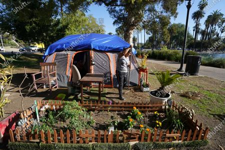 """Woman rakes her """"Love Garden"""" outside one of the remaining tents at the Echo Park homeless encampment at Echo Park Lake in Los Angeles . Los Angels Councilmember Mitch O'Farrell, 13th District, is pushing back against the notion of a """"sweep."""" He said Wednesday that more than 120 of the Echo Park homeless people have now been moved into transitional housing at Roomkey and Homekey sites"""