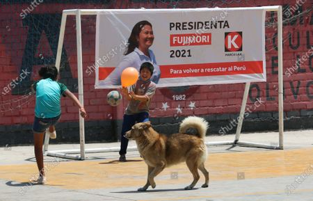Boys play soccer in front of a campaign billboard featuring presidential candidate and daughter of imprisoned ex-President Alberto Fujimori, Keiko Fujimori, of the Popular Force party, before her arrival to campaign in Los Olivos on the outskirts of Lima, Peru, . Peru's general election is set for April 11
