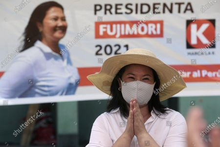 Wearing a mask to curb the spread of the new coronavirus, presidential candidate Keiko Fujimori, daughter of imprisoned ex-President Alberto Fujimori, waves to supporters as she campaigns for the Popular Force party in Los Olivos on the outskirts of Lima, Peru, . Peru's general election is set for April 11