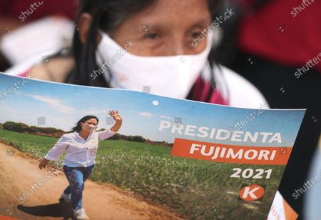 Wearing masks to curb the spread of the new coronavirus, a supporter of presidential candidate Keiko Fujimori, daughter of imprisoned ex-President Alberto Fujimori, holds a calendar featuring her photo as Fujimori campaigns for the Popular Force party in Los Olivos on the outskirts of Lima, Peru, . Peru's general election is set for April 11