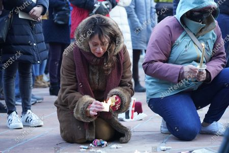 Peggy Lynn Cormier, center, joins other mourners in lighting tea candles, at a vigil outside the courthouse for the victims of a mass shooting at a grocery store, in Boulder, Colo. Cormier's friend, shop owner Tralona Bartkowiak, was one of the victims in the massacre