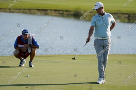 Matt Jones of Australia and his caddie look at the 16th hole during the final round of the Honda Classic golf tournament, in Palm Beach Gardens, Fla