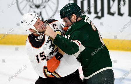 Anaheim Ducks' Ryan Getzlaf (15) and Minnesota Wild's Carson Soucy (21) fight during the first period of an NHL hockey game, in St. Paul, Minn. Both players received penalties