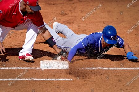 Kansas City Royals' Whit Merrifield dives back safely on a pick-off attempt as Los Angeles Angels' Albert Pujols (5) makes the tag during the third inning of a spring training baseball game, in Tempe, Ariz