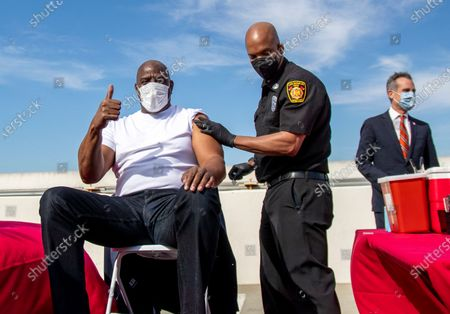 Magic Johnson gives a thumbs up after getting a vaccine from Los Angeles Fire Chief Ralph Terrazas on the rooftop of parking structure at USC as a part of a vaccination awareness event at USC on March 24, 2021 in Los Angeles, California. L.A. Mayor Eric Garcetti is in the background. (Gina Ferazzi / Los Angeles Times)